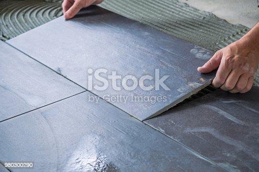 istock Worker`s hands placing ceramic floor tile 980300290