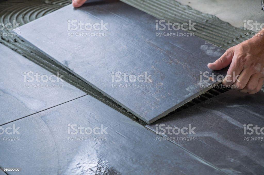 Worker`s hands placing ceramic floor tile stock photo