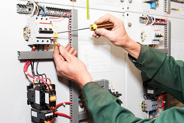 労働者の手電気パネルに近く、電動ネジ回し - 電気部品 ストックフォトと画像