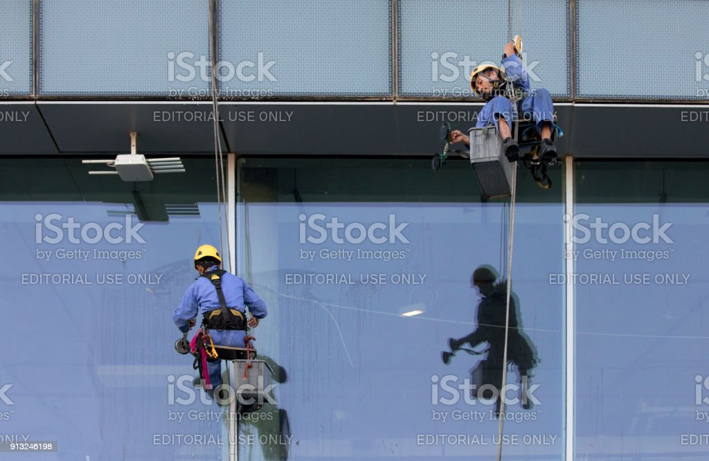 workers hanging down a buiding to wash windows stock photo