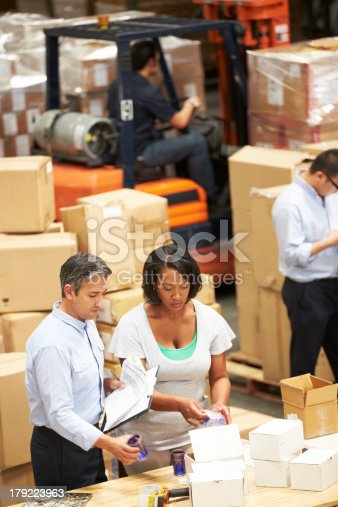 istock Workers in a warehouse talking 179223963