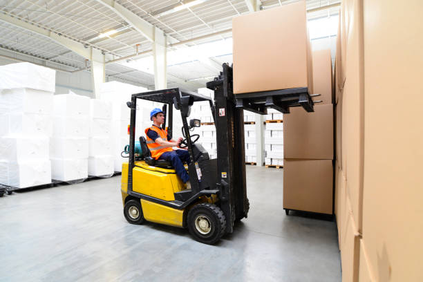 Workers in a warehouse - transport of goods with a forklift truck stock photo