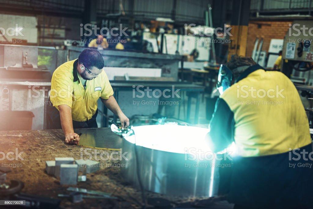 Arbeiter in australischen Fabrik Schweißen die Metallteile für das Endprodukt Lizenzfreies stock-foto