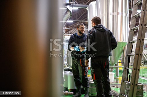 istock Workers in brewery exchanging a few words while working 1158551650