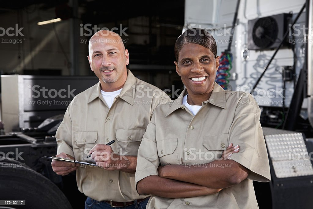 Workers in garage with semi-truck stock photo