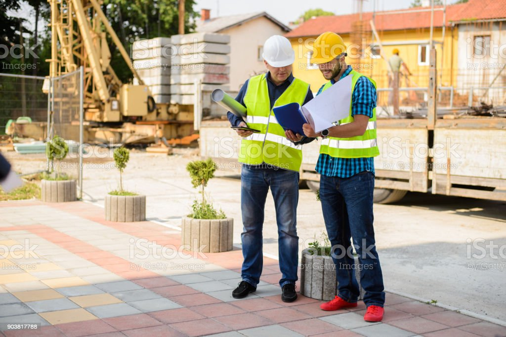 Workers in hardhat and green jacket posing on building site stock photo