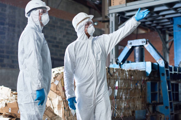 Workers in Hazmat Suits at Modern Factory stock photo