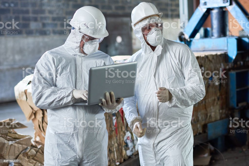 Workers in Hazmat Suits at Modern Recycling Factory stock photo