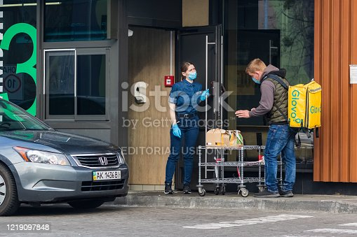 Kyiv Ukraine - April 10 2020: Workers in protective masks and protective gloves pass orders to a delivery service representative in a fast food restaurant. Quarantine in large cities.