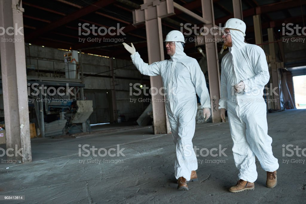 Workers in Protective Suits Crossing Workshop at Modern Factory stock photo