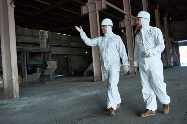 workers in protective suits crossing workshop at modern factory - white suit stock photos and pictures