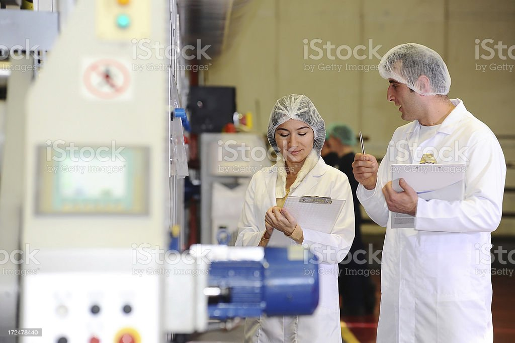 Workers in the factory wearing protective workwear stock photo