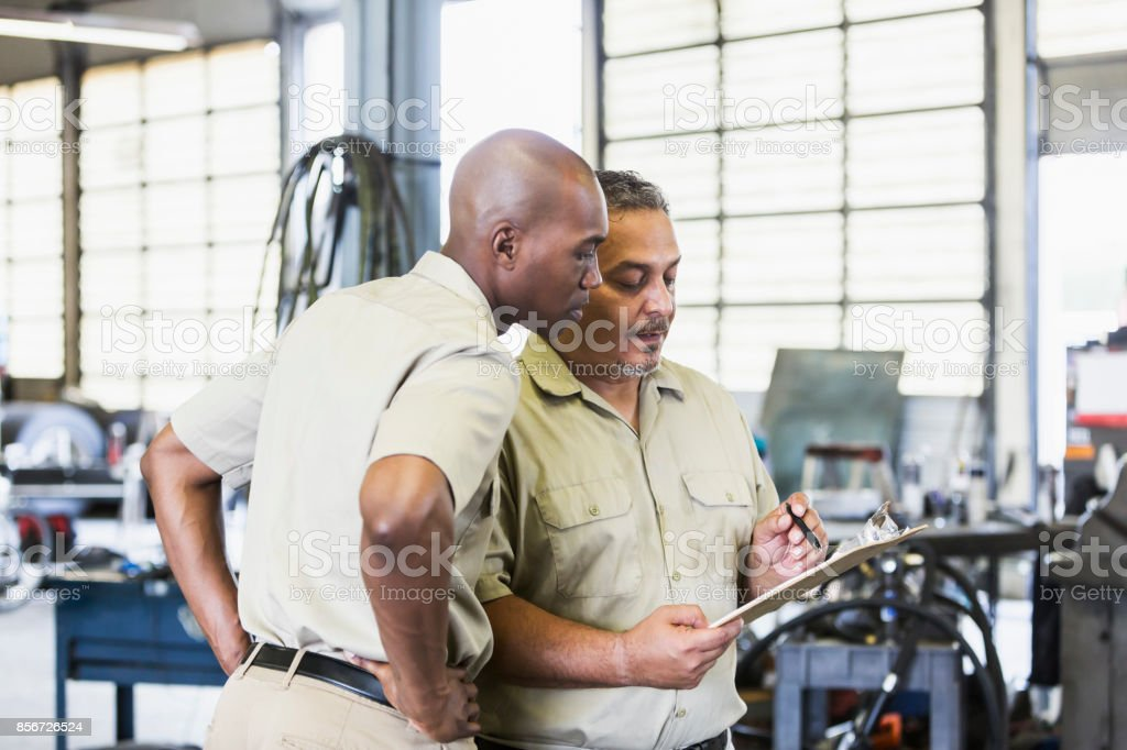 Workers in truck repair shop stock photo