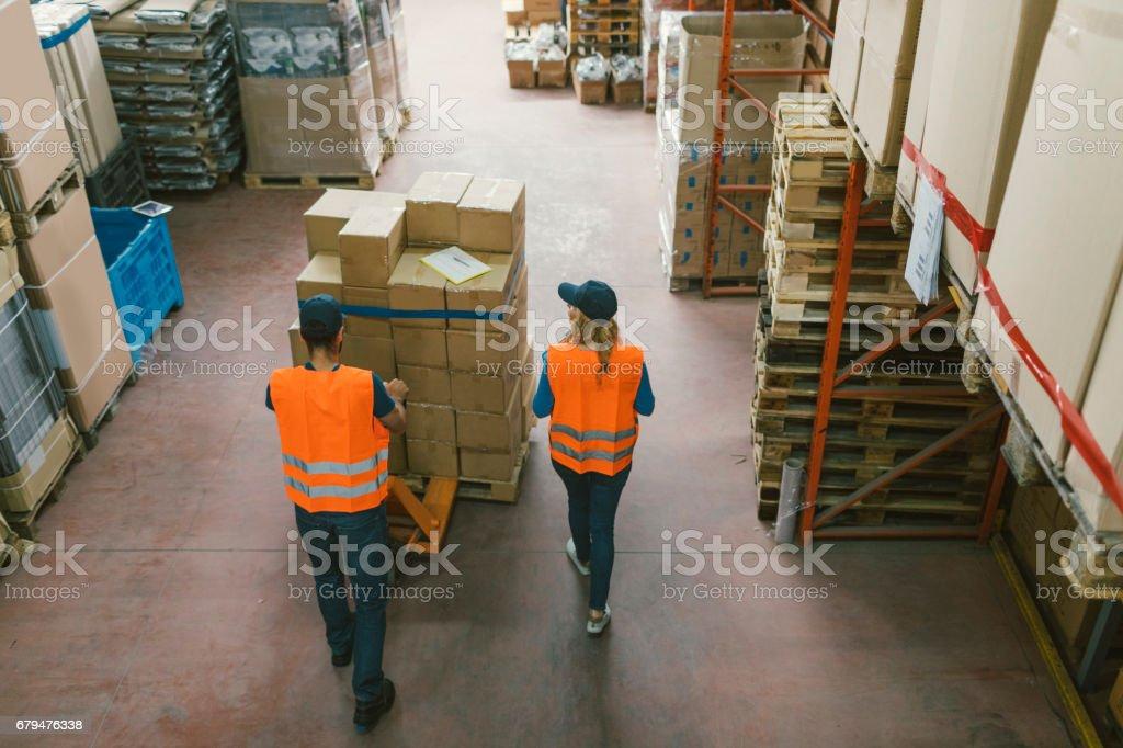 工人在檢查商品的倉庫 免版稅 stock photo