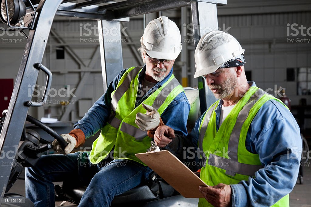 Workers in warehouse with forklift stock photo
