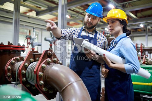 Portrait of two factory workers pointing away while working with piping and machines in modern workshop, copy space