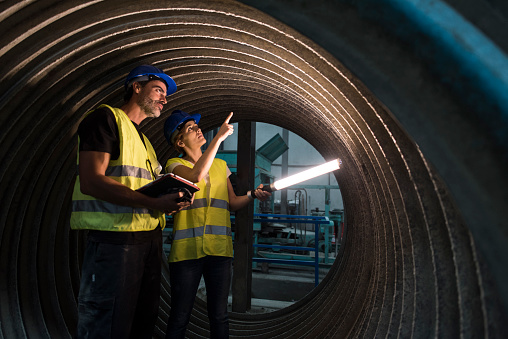workers inspects the inside of a tubular structure in a cement and infrastructure construction company with led