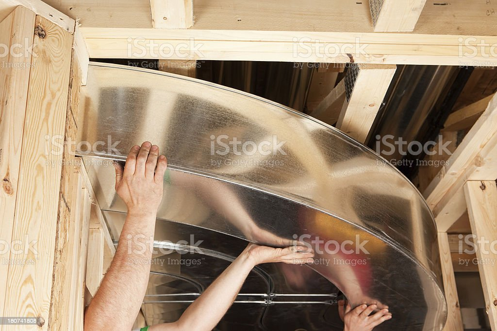 Workers Installing Complex HVAC Galvanized Duct Sections stock photo