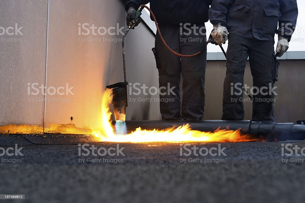 Workers installing roofing felt with heat stock photo