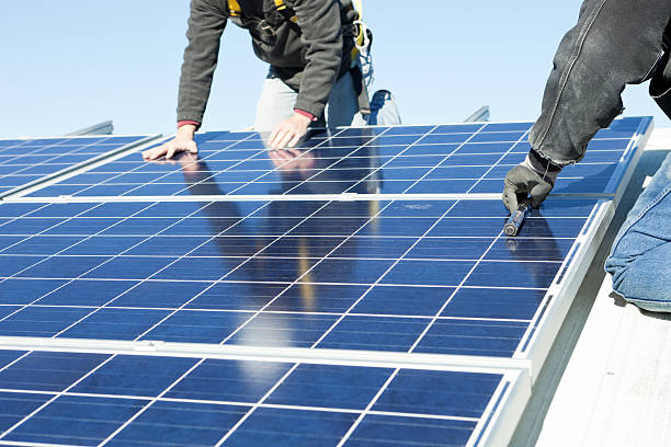 Worker's Installing Rooftop Solar Panels stock photo