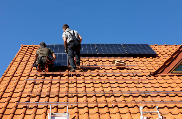 Workers installing solar electric panels on a house roof