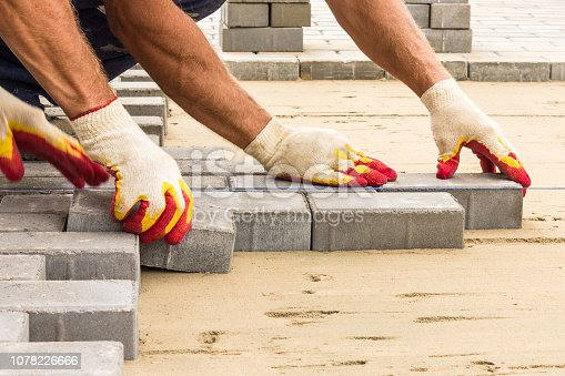 workers lay paving tiles, construction of brick pavement, men's hands in gloves, close up architecture background