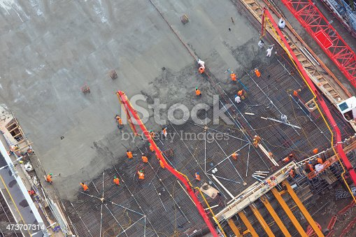 unrecognizable workers laying and spreading concrete - aerial view