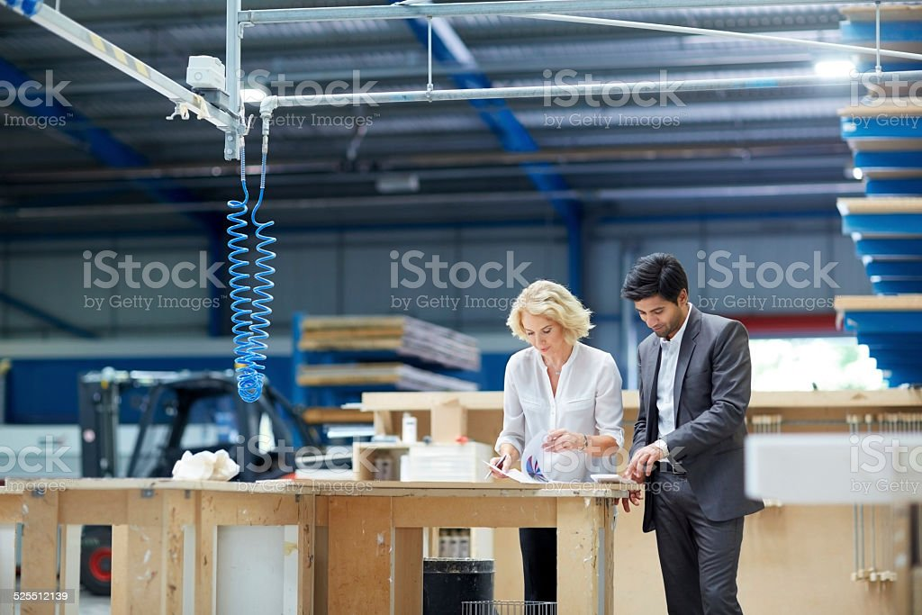 Workers looking at paperwork in factory stock photo