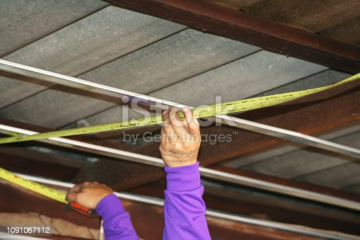 Workers measuring wood under roof, prepare for ceiling installation.