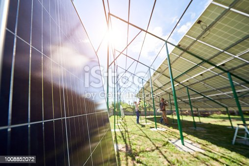 istock Workers mounting innovative solar panels on green metal construction 1008852072