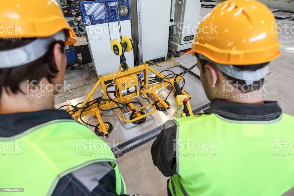Travailleurs près de tôle, appareil de levage - Photo de Acier libre de droits