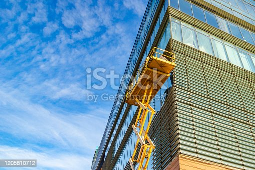 Workers on a Scissor Lift Platform at a construction site. Men at work. Scissor lift platform ensures safe operation at height.