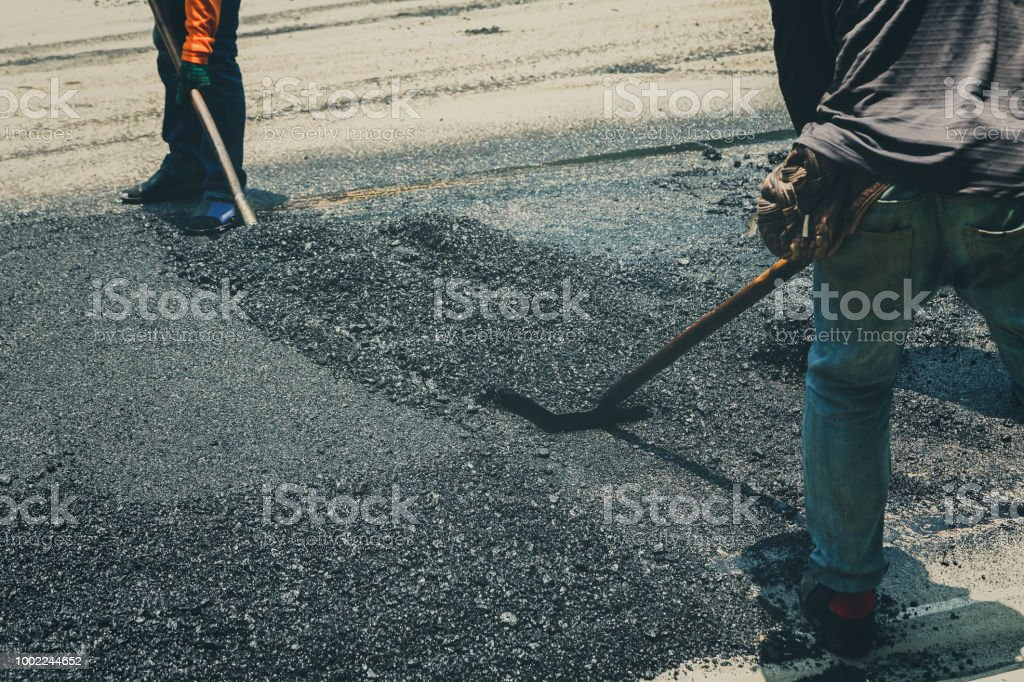 Workers on Asphalting paver machine during Road street repairing works stock photo