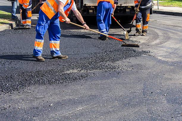 lavoratori su asphalting road - asfalto foto e immagini stock