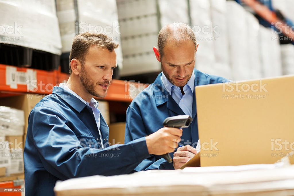 Workers on forklift discussing at warehouse stock photo