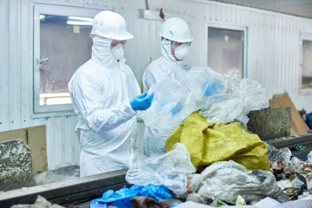 Workers on Waste Processing Plant Portrait of two workers wearing biohazard suits at waste processing plant sorting recyclable plastic and cardboard on conveyor belt decontamination stock pictures, royalty-free photos & images