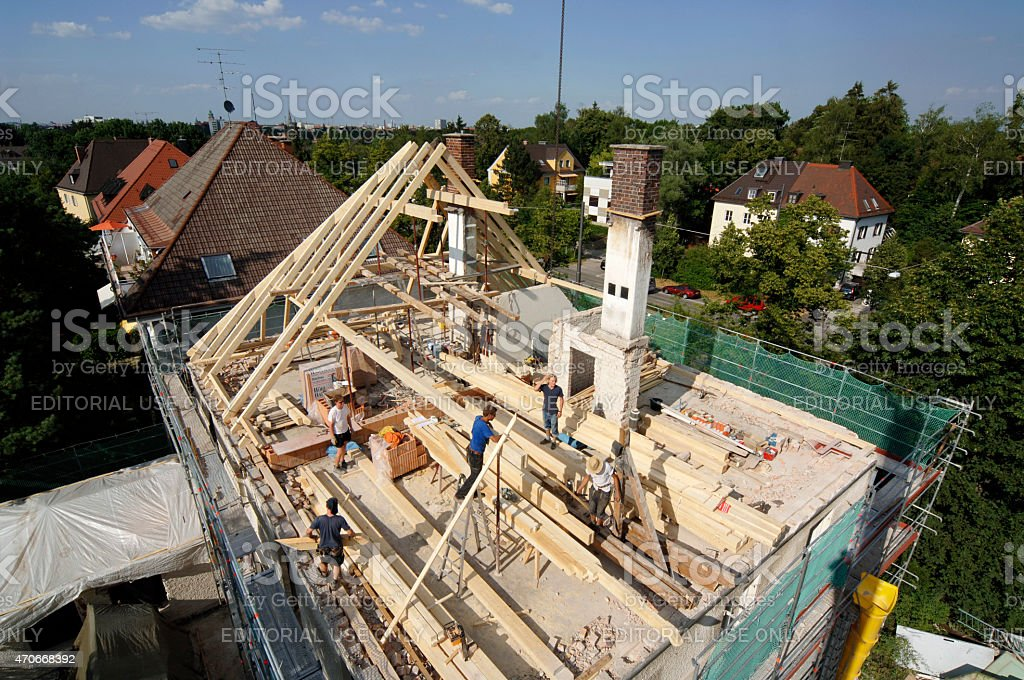 Workers on wooden roof truss with blue sky stock photo