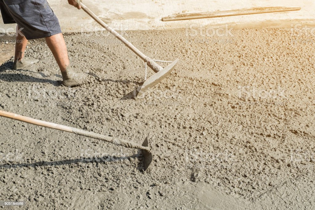 Workers person not wearing dirt boots digging with hoe (shovel) on concrete floor, Construction workers leveling concrete pavement. Upgrade to residential street leveling concrete slab, working place stock photo