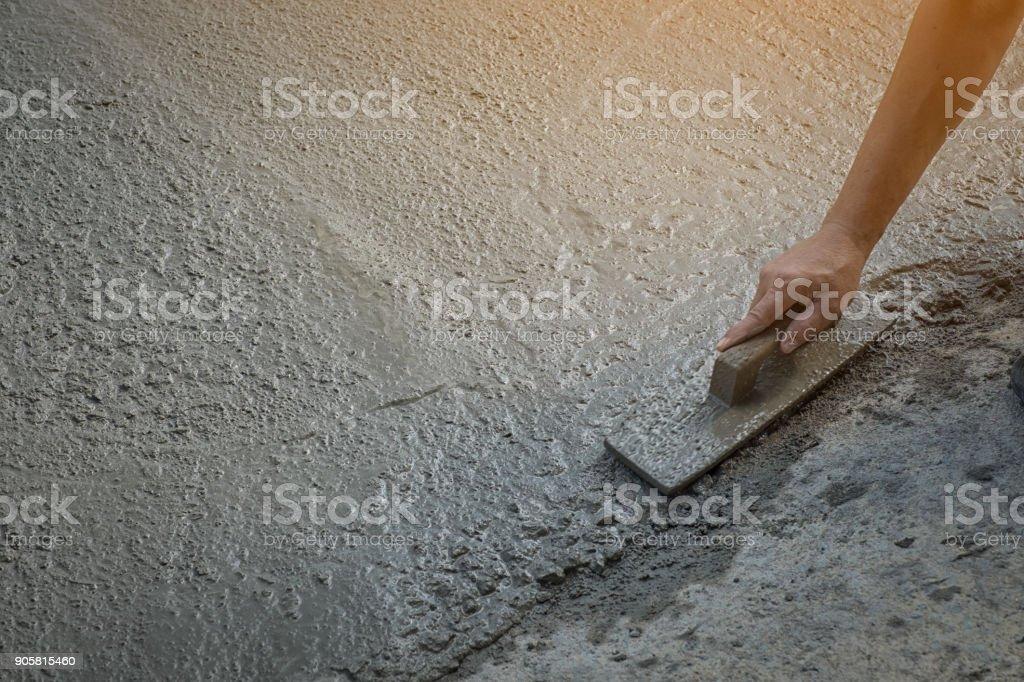 Arbeiter Trägers nicht Schmutz Stiefel Graben mit Hacke (Schaufel) auf Betonboden, Bauarbeiter, die Nivellierung Betonfahrbahn. Aktualisieren Sie auf Wohn Straße Nivellierung Betonplatte, Arbeitsplatz – Foto