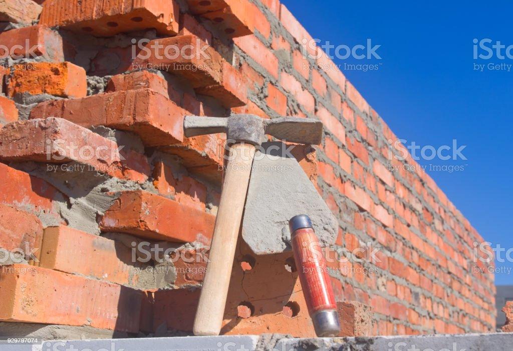 [Imagen: workers-pick-hammer-and-trowel-on-buildi...d929797074]