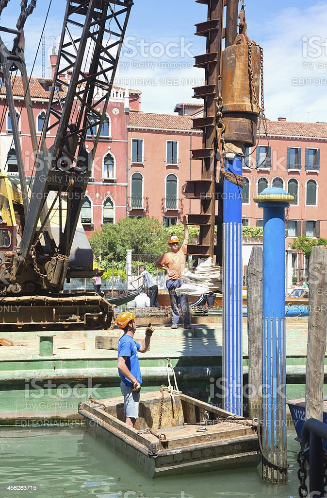 Workers plant a pole in Canal Grande, Venice royalty-free stock photo