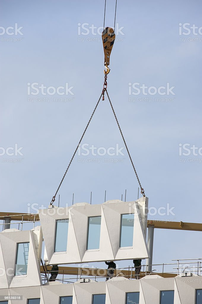 Workers postioning a hoisted facade element stock photo
