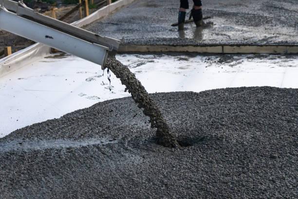 i lavoratori versano la fondazione per la costruzione di un edificio residenziale utilizzando betoniere mobili. - calcestruzzo foto e immagini stock
