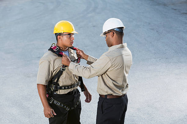 Workers, putting on safety harness Multi-ethnic workers (20s, 30s) with hardhats, putting on safety harness. safety harness stock pictures, royalty-free photos & images