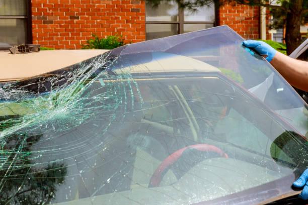arbeiter entfernen abgestürzte windschutzscheibe eines autos im autodienst - fensterbauer stock-fotos und bilder
