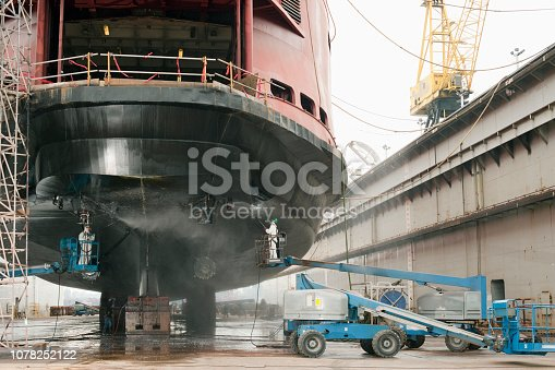 Workers repairing ferry boat ship in dry dock