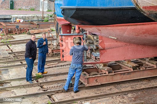 Urk, The Netherlands - September 07, 2019: Workers repairing rudder of ship at shipyard in Dutch fishing village Urk