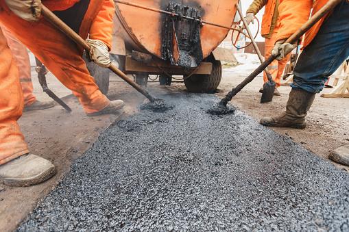 Working men in orange overalls repairing the road, shovels fill asphalt road repair