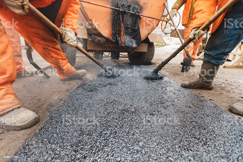 Workers repairing the road with shovels fill asphalt driveway repair stock photo
