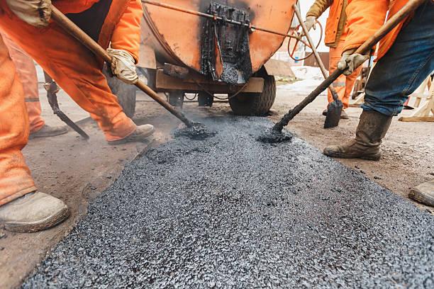 lavoratori della riparazione della strada con pale riempire asfalto vialetto di riparazione - asfalto foto e immagini stock